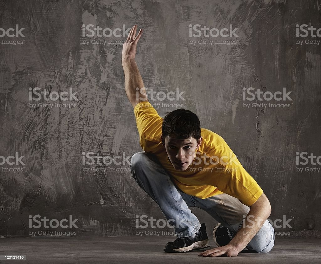 Young man dancing against grunge wall royalty-free stock photo