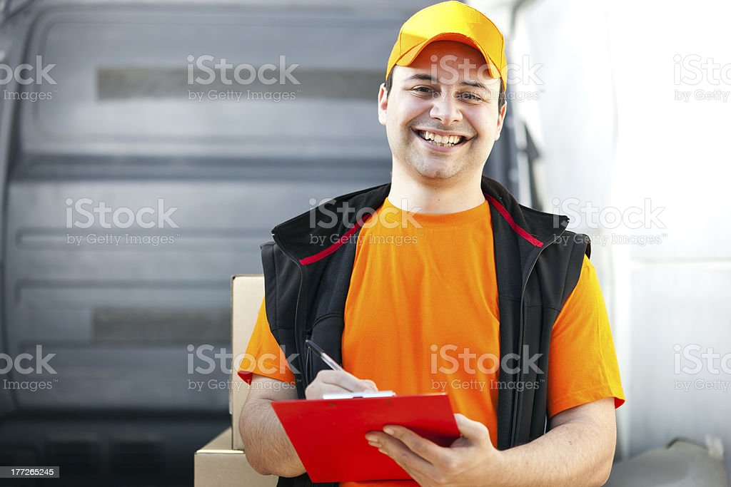 Young man delivering a box and signing form stock photo