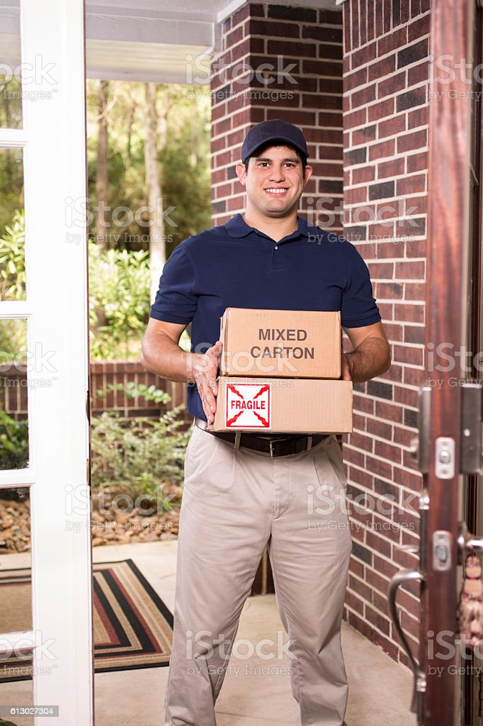 Young man delivers packages to customer at home. stock photo