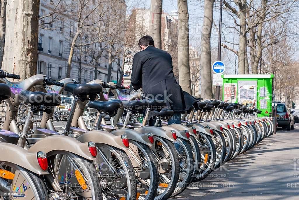 Young man depositing his bike at the Velib station stock photo