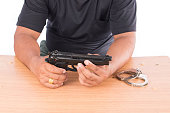 Young man disassembled gun on table