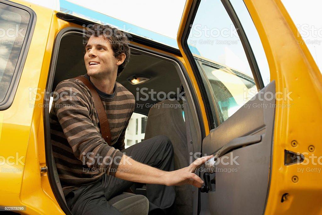 Young Man Disembarking Taxi stock photo