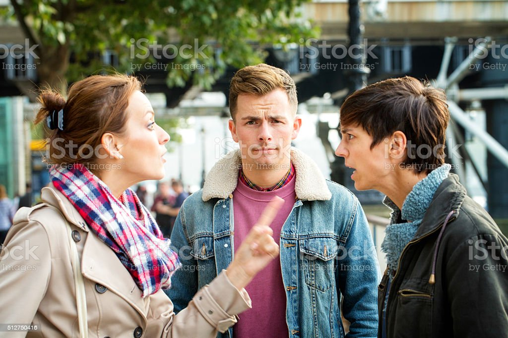 Young man dismayed as his girlfriend argues with ex stock photo