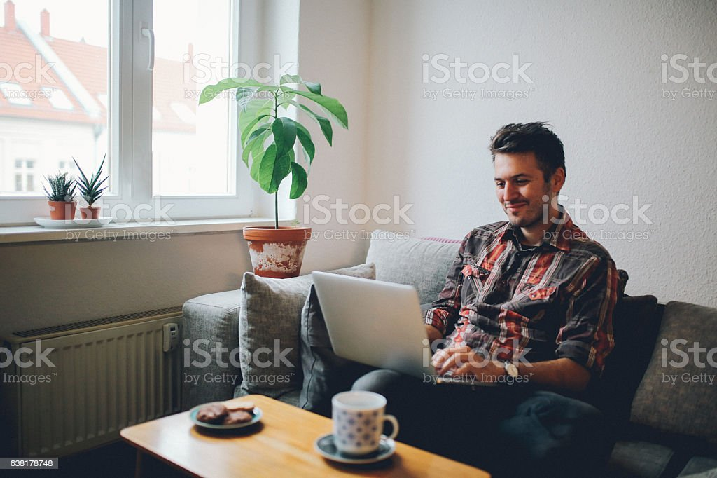 Young man doing a freelance job from home stock photo