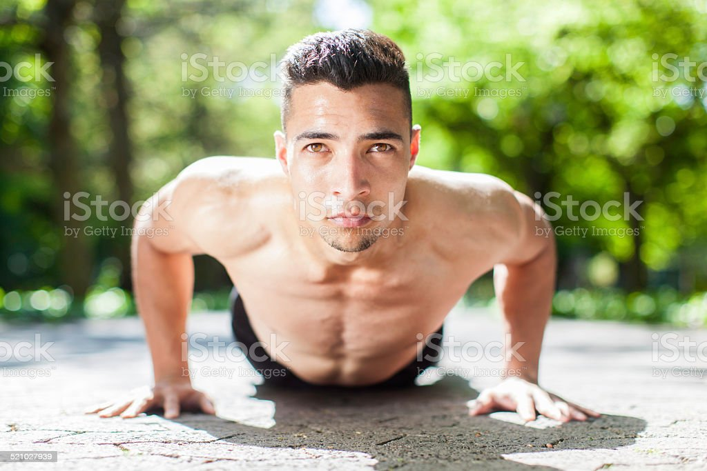 young man doing a push up in the city park stock photo