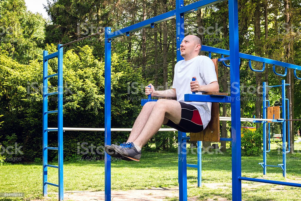 young man doing abdominal exercise in summer park. stock photo