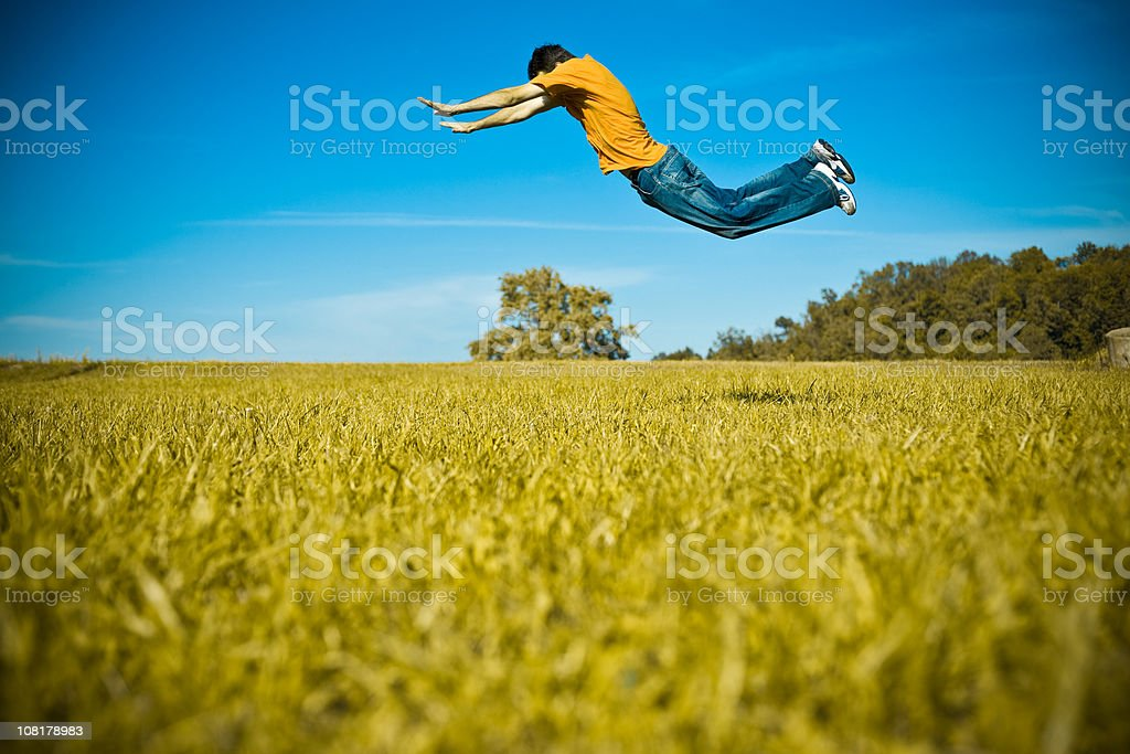 young man doing acrobatic trick in the field royalty-free stock photo
