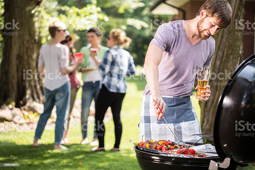 Young man doing barbecue stock photo