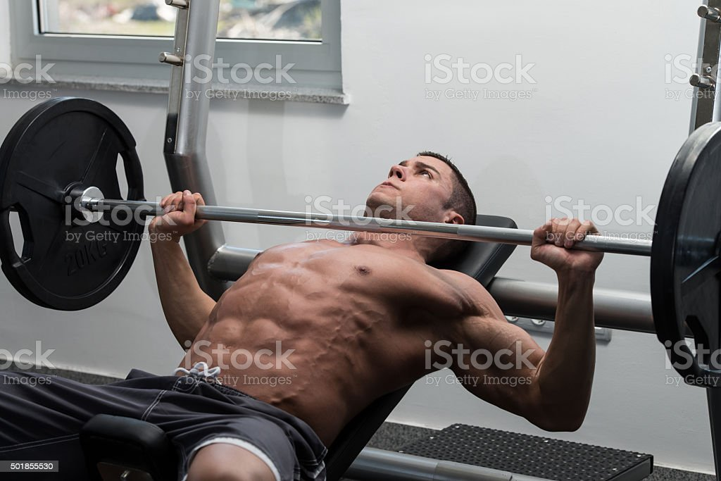 Young Man Doing Bench Press Exercise For Chest stock photo