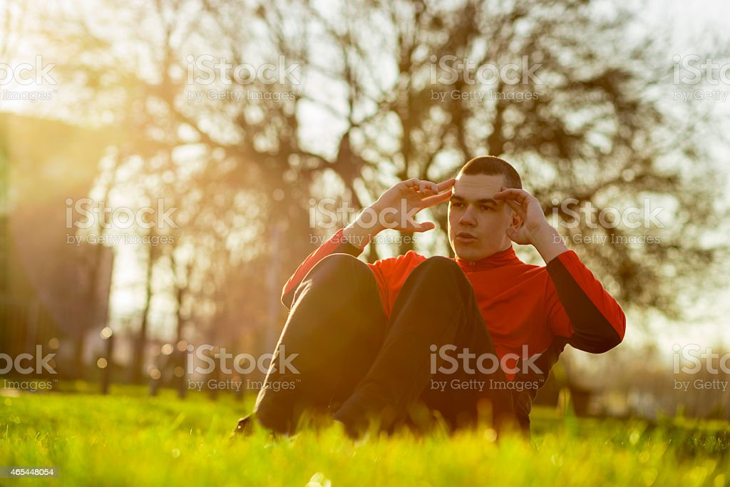 Young man doing crunches on the grass stock photo