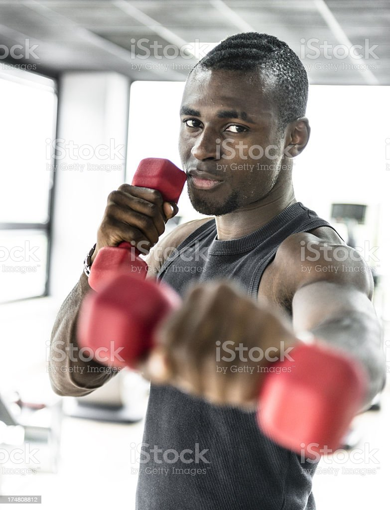 Young man doing exercise on a gym with dumbbell royalty-free stock photo