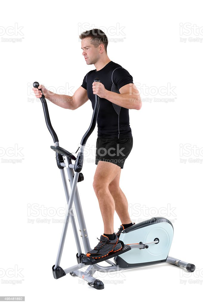young man doing exercises on elliptical trainer stock photo