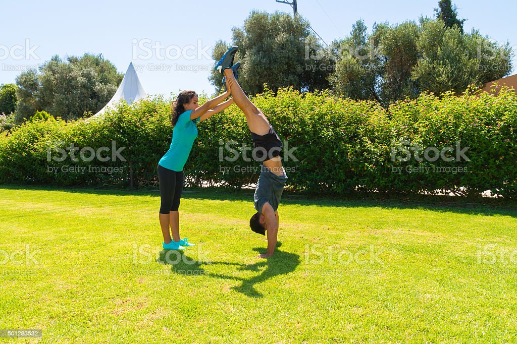 Young man doing handstands in the park with trainer assistance stock photo