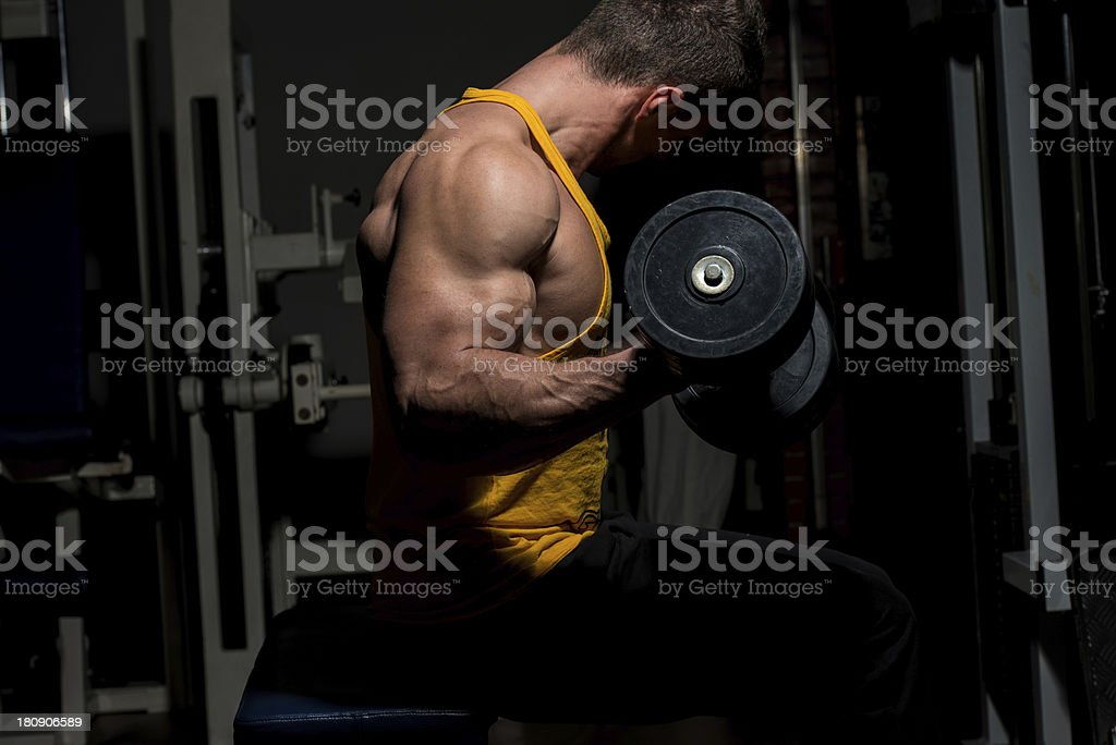 young man doing heavy weight exercise for biceps royalty-free stock photo