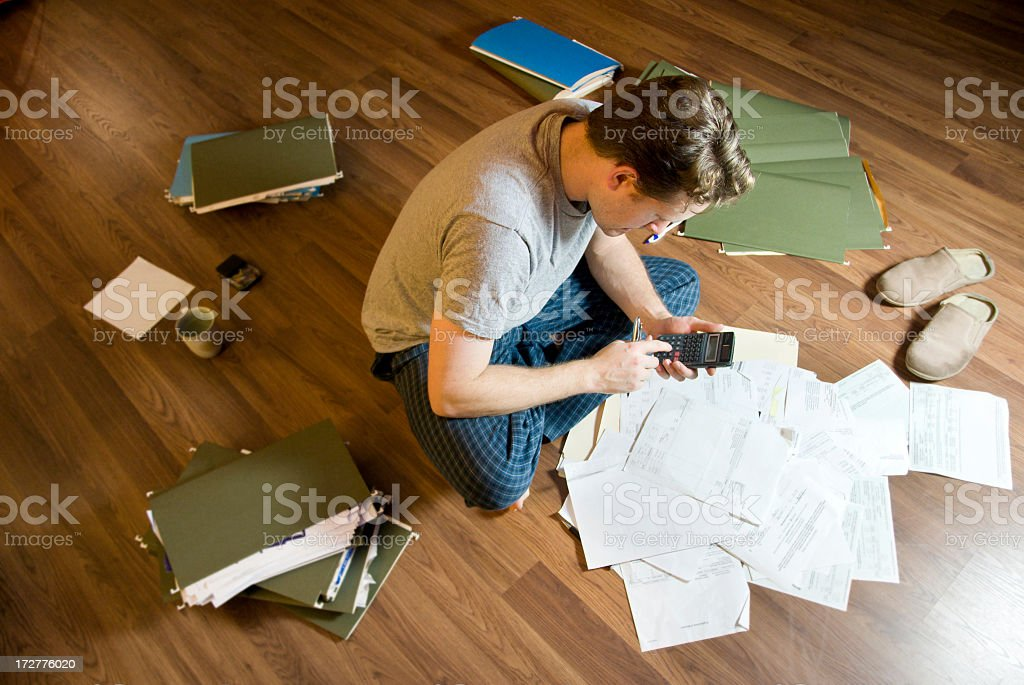 A young man doing his taxes on a floor covered in papers stock photo