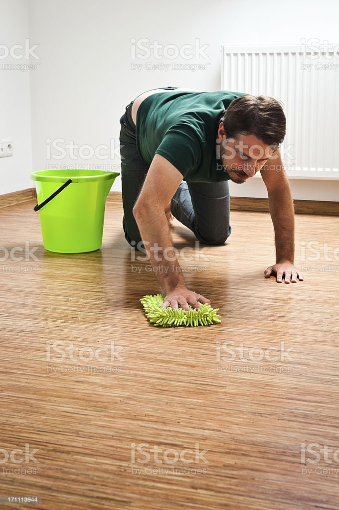 Young man doing houseworks, he is washing the floor royalty-free stock photo