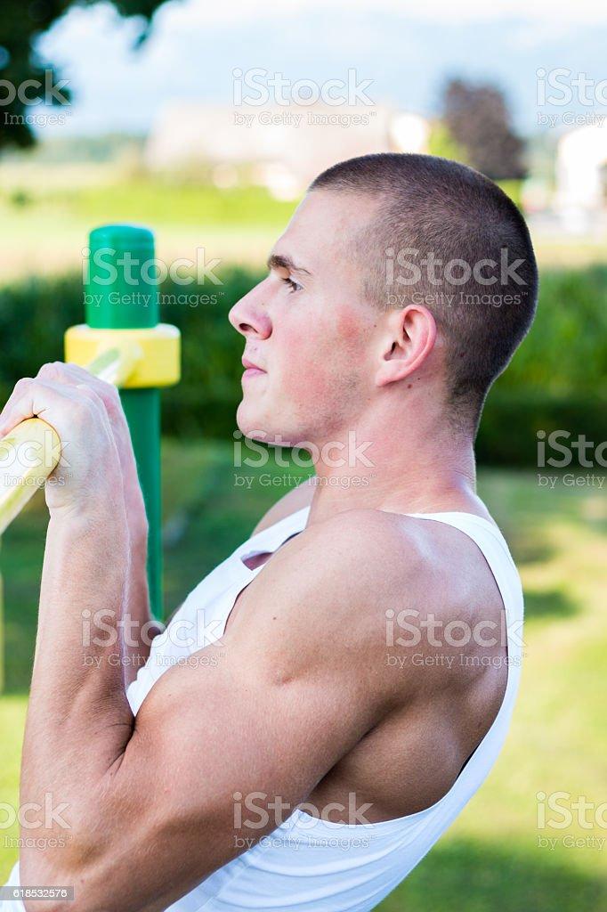 young man doing pull ups on horizontal bar outdoors stock photo