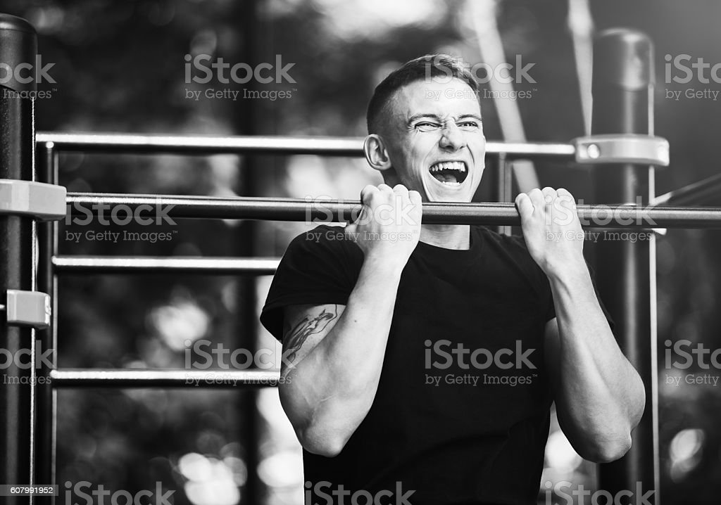 Young man doing pull ups on horizontal bar outdoors, workout stock photo