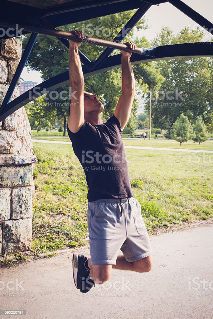 Young man doing pull-ups stock photo