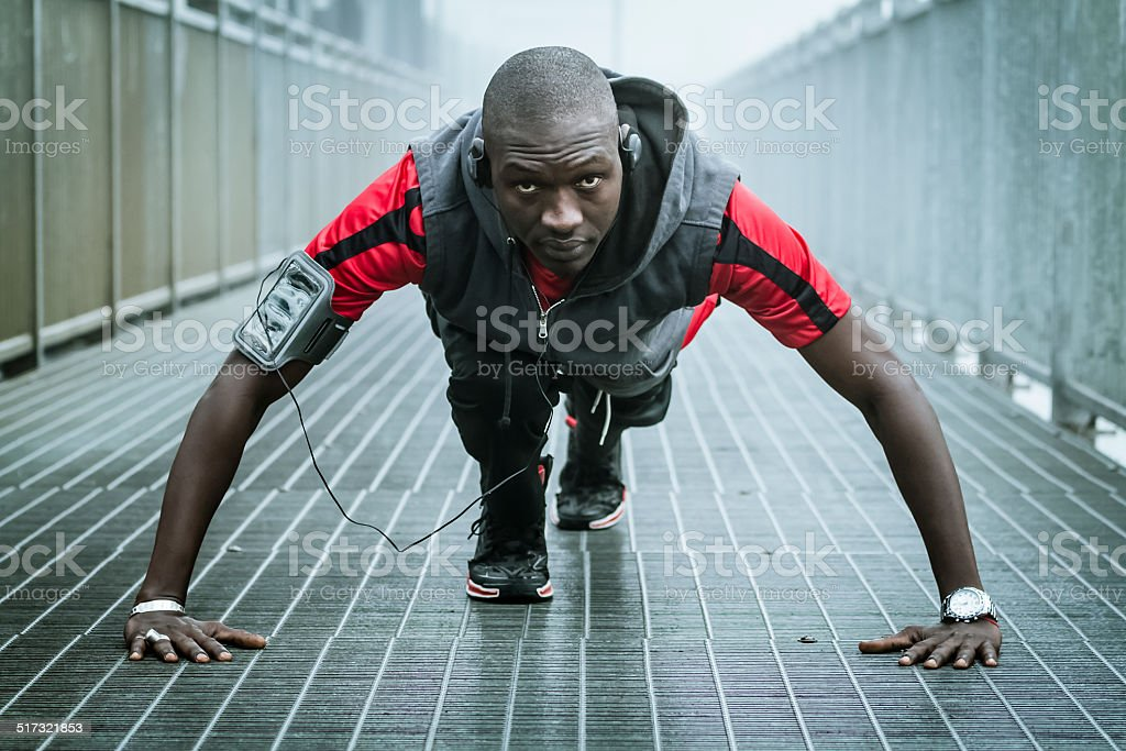 Young man doing push-ups on iron bridge stock photo