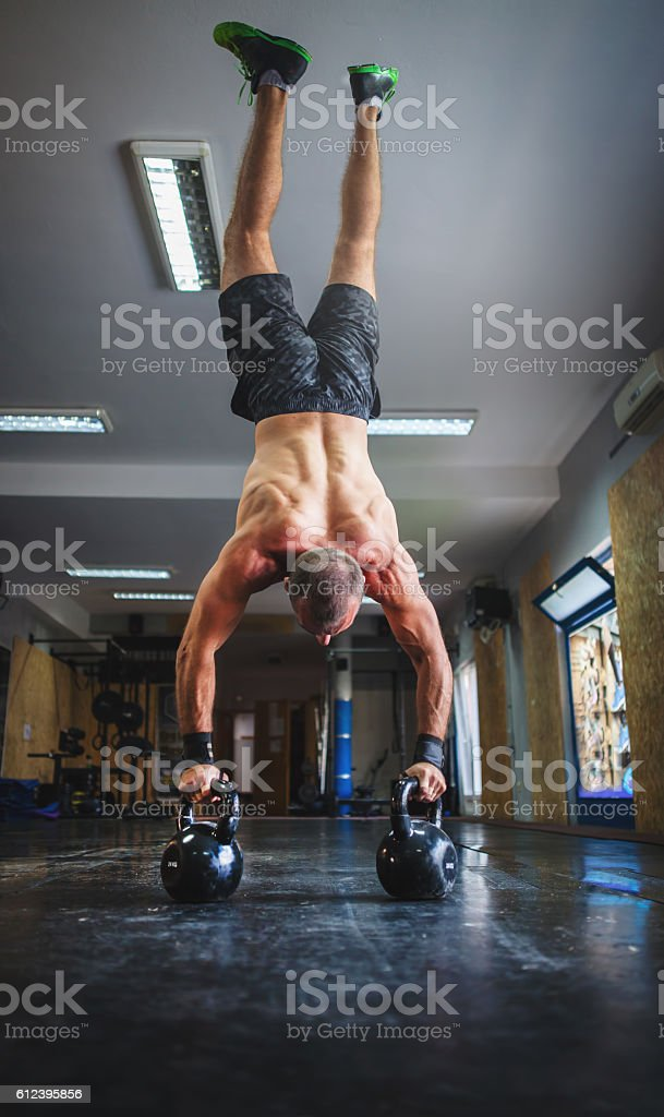 Young man doing pushups with kettle bells at the gym stock photo