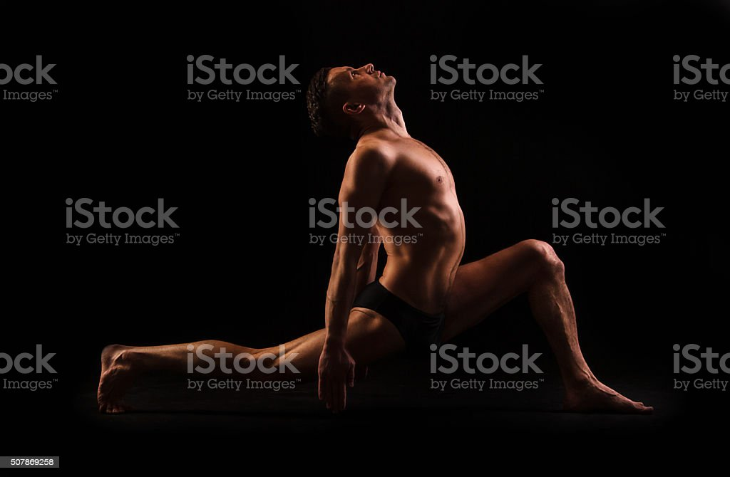 young man doing yoga and gymnastics,  deep lunge leg stock photo