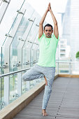 Young Man Doing Yoga Tree Pose in Fitness Center