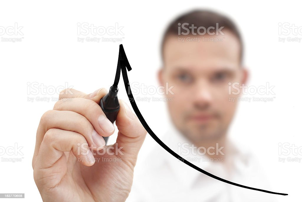 Young man drawing an arrow with black marker on glass. royalty-free stock photo