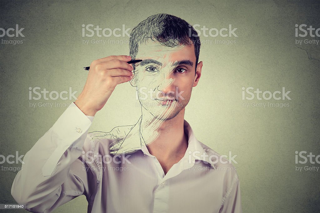 Young man drawing self portrait face stock photo