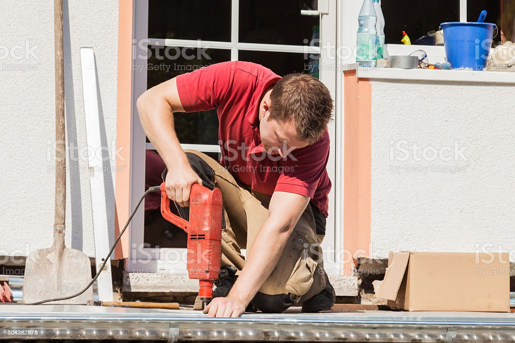Young man drilling a hole with an impact drill stock photo