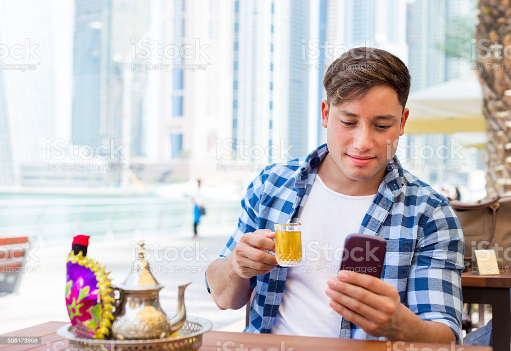 Young man drink arab tea and typing messages in Dubai stock photo