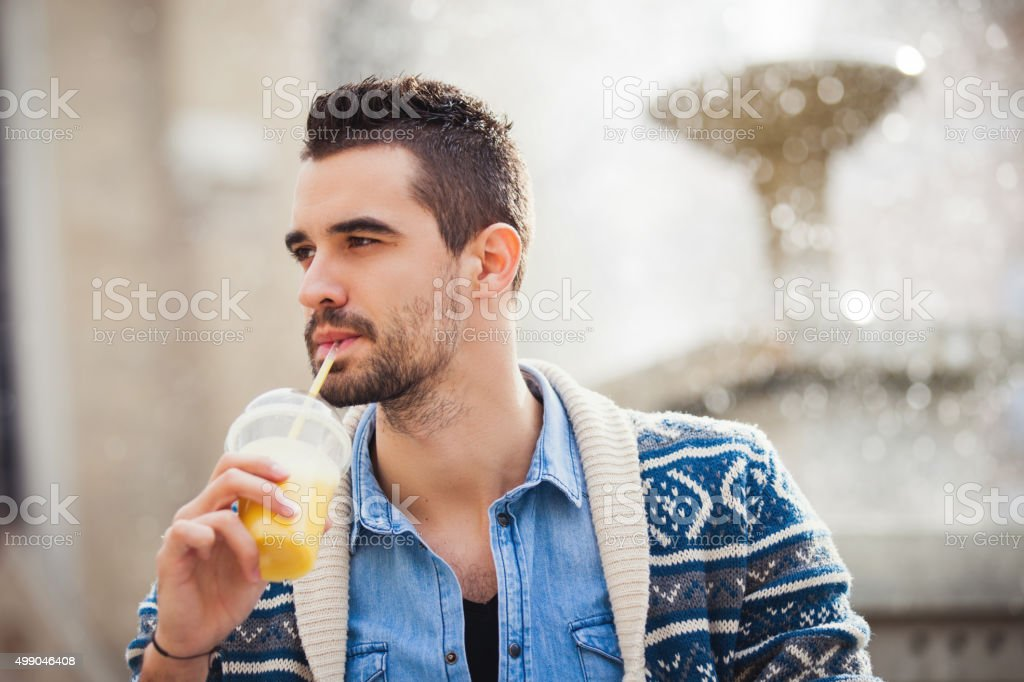 Young man drinking a yellow smoothie stock photo