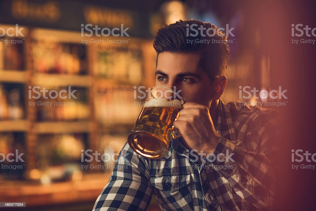 Young man drinking beer in a bar and looking away. stock photo