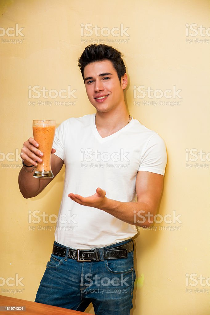 Young man drinking big glass of healthy fruit smoothie stock photo