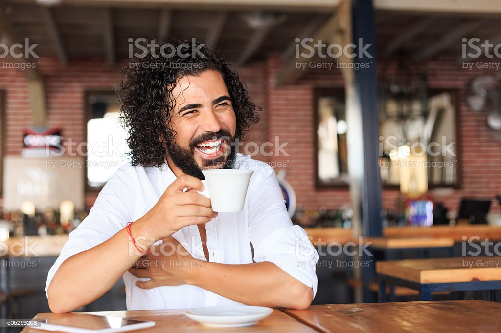 Young man drinking coffee at bar stock photo