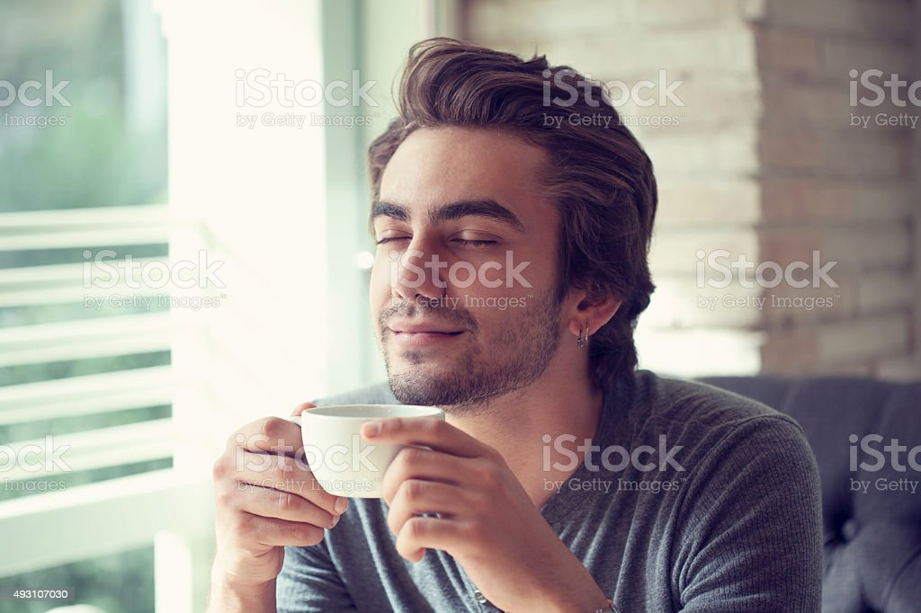 Young man drinking coffee in cafe stock photo
