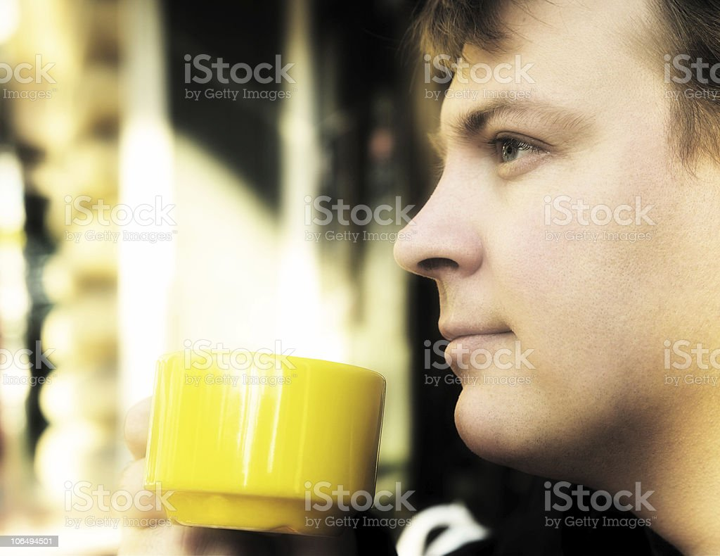 Young man drinking coffee outside stock photo