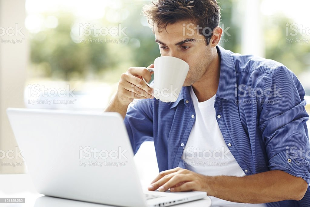 Young man drinking coffee while using at laptop royalty-free stock photo