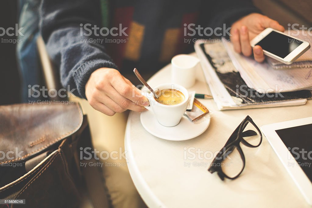 Young man drinking espresso and texting in a cafe stock photo