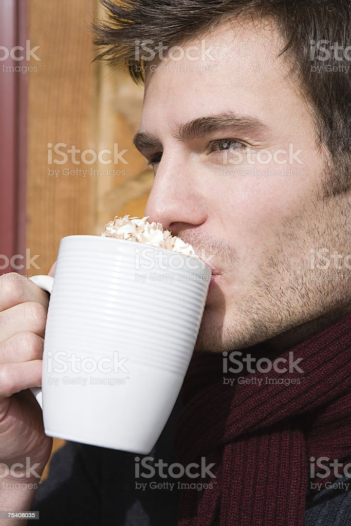 Young man drinking hot chocolate stock photo