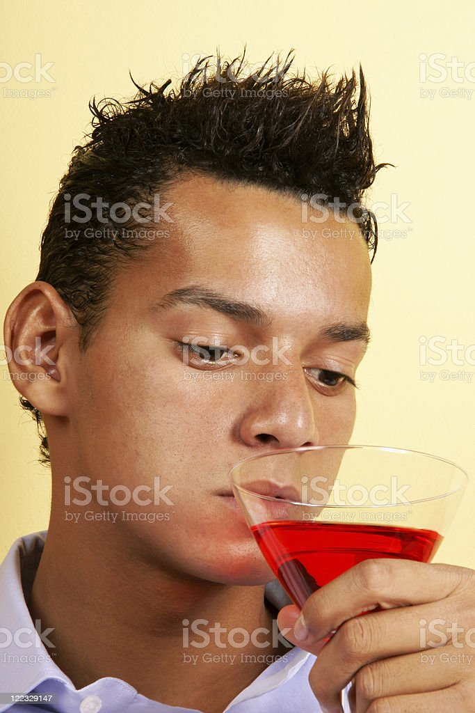 Young man drinking red cocktail stock photo