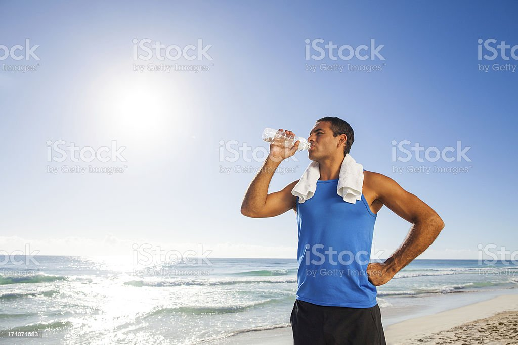 Young man drinking water after exercising royalty-free stock photo