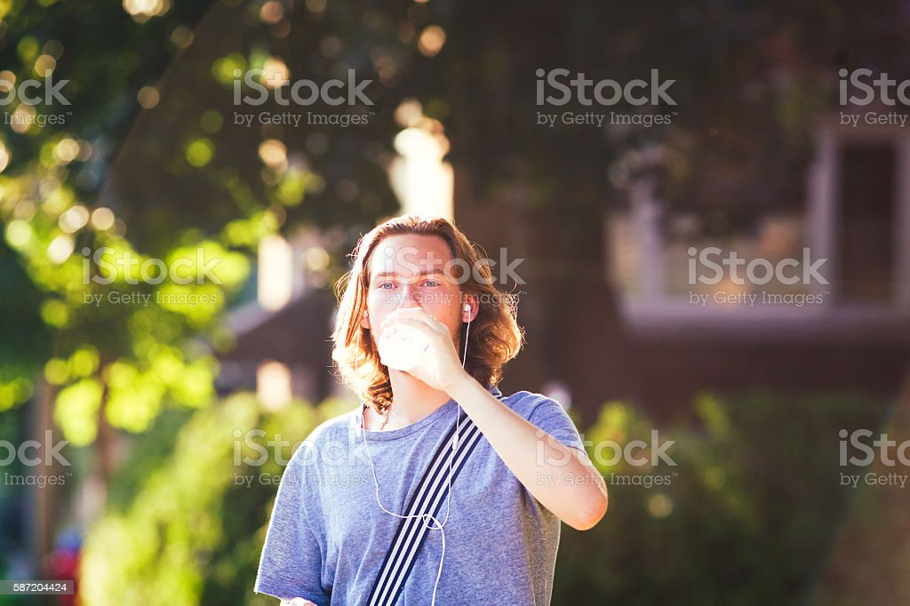 Young man drinking water outdoors with earbuds on stock photo