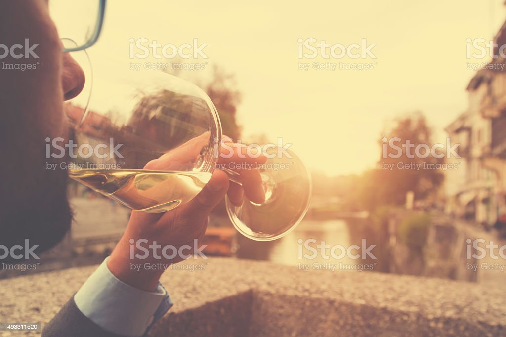 Young man drinking wine outdoors. stock photo