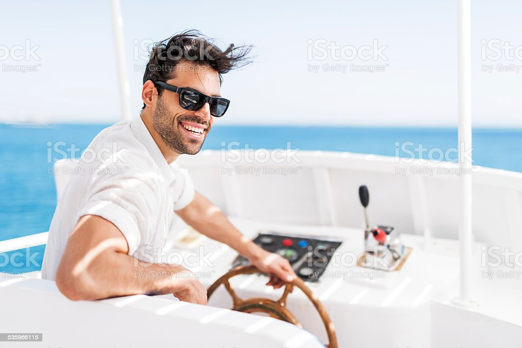 Young man driving a boat. stock photo