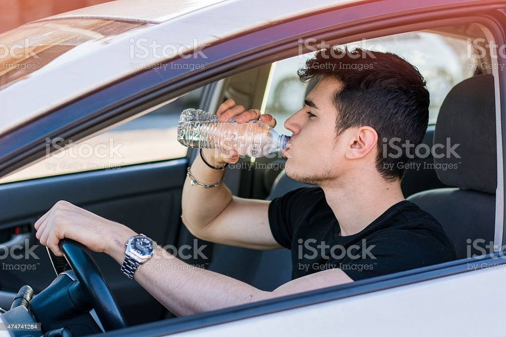 Young man driving car and drinking water from bottle stock photo