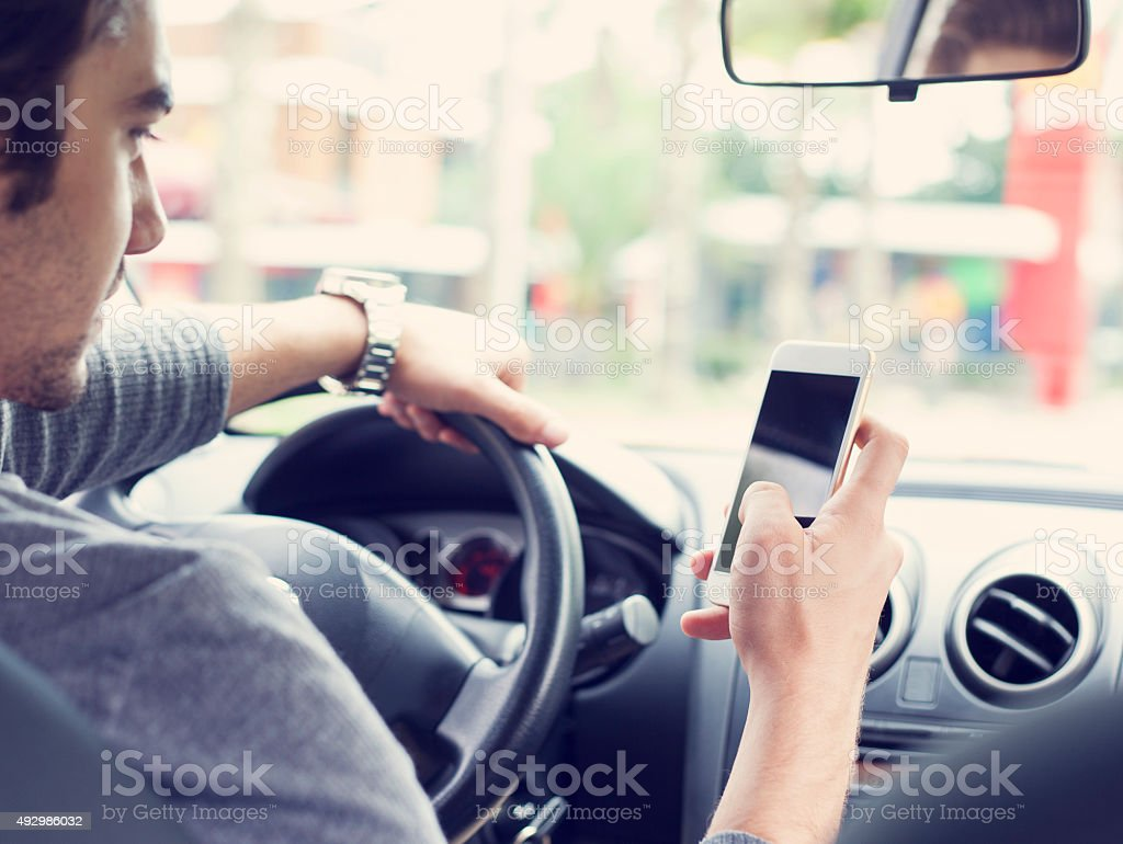 Young man driving car and using mobile phone stock photo