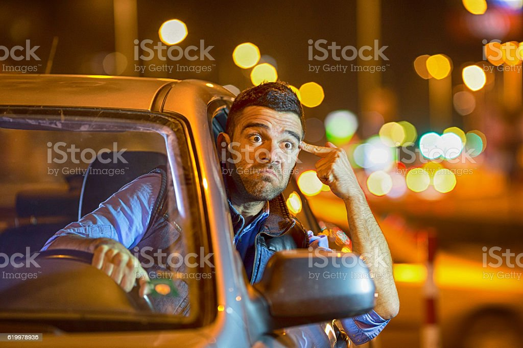 Young man driving car at night angry to traffic stock photo