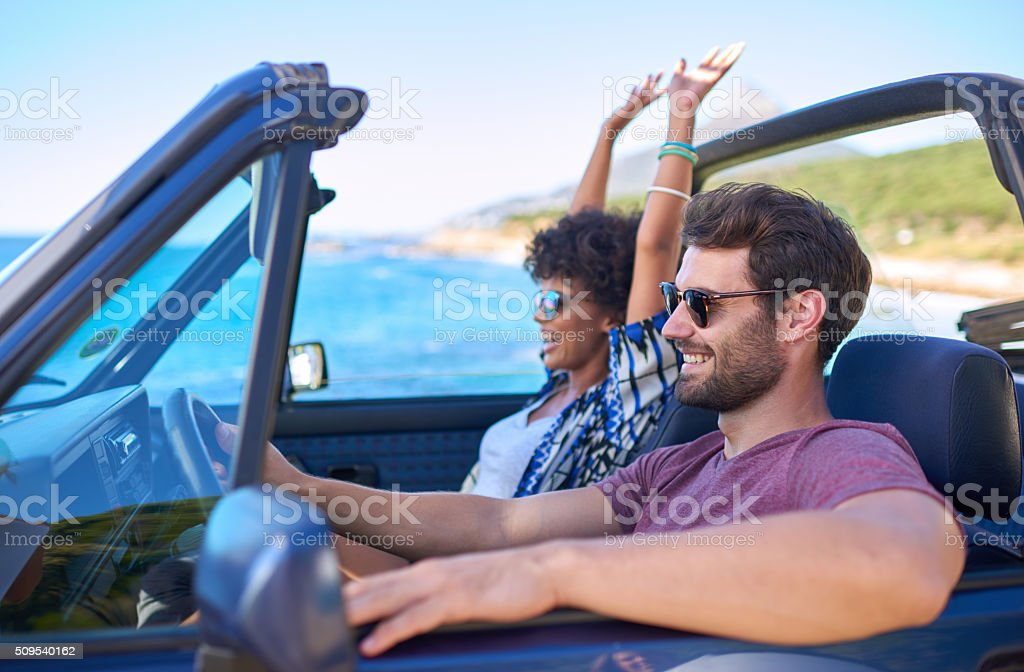 Young man driving car with his girlfriend in roadtrip stock photo