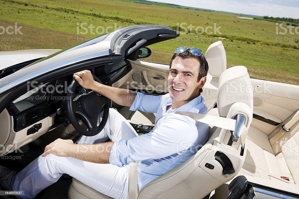 Young man driving his cabriolet and looking at the camera. royalty-free stock photo